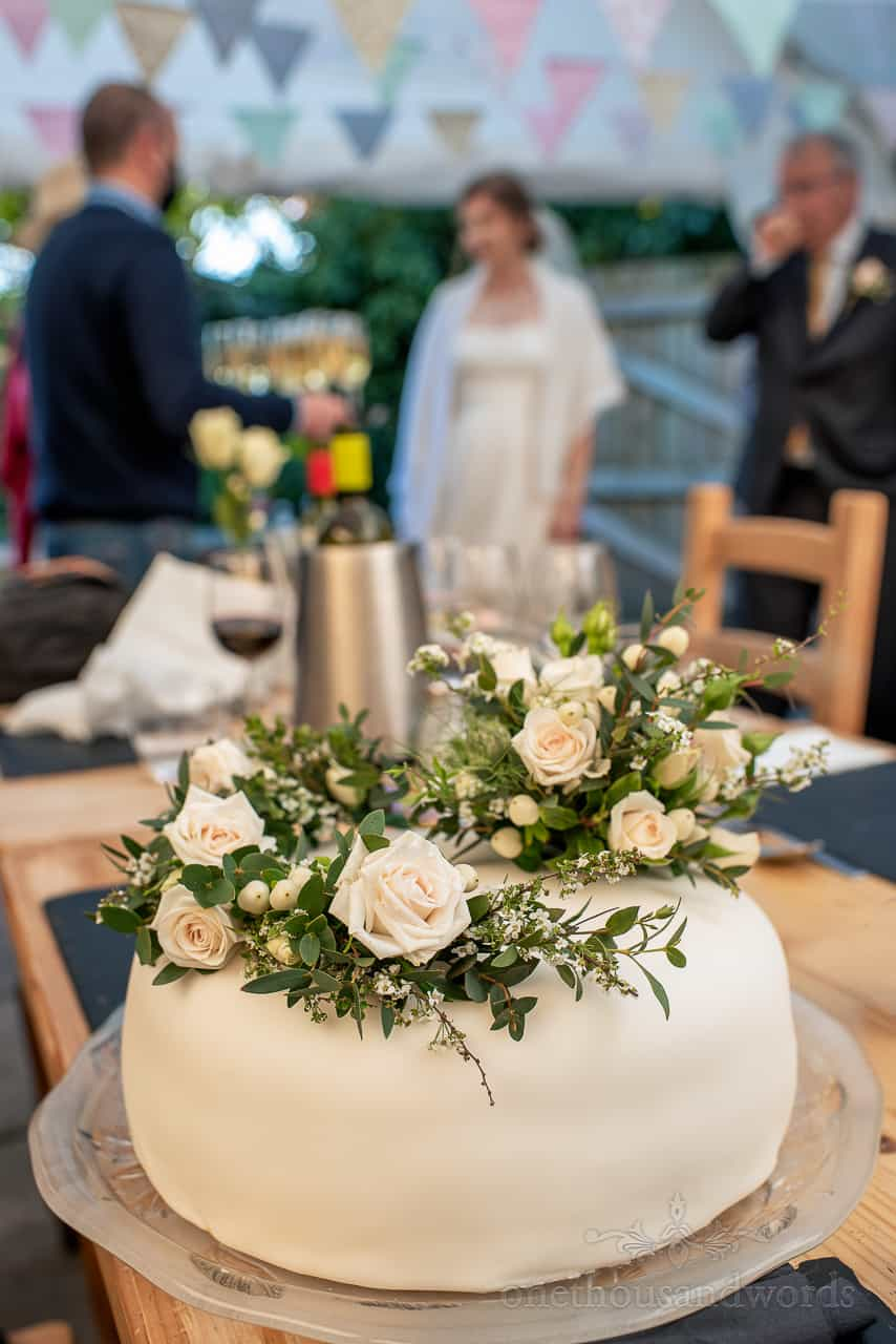 Wedding detail photo of single tier white wedding cake decorated with white roses and green foliage