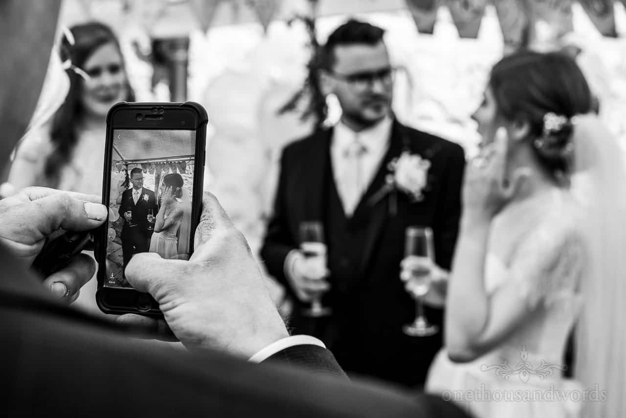 Black and white wedding photo of guest taking bride and groom photos on mobile phone