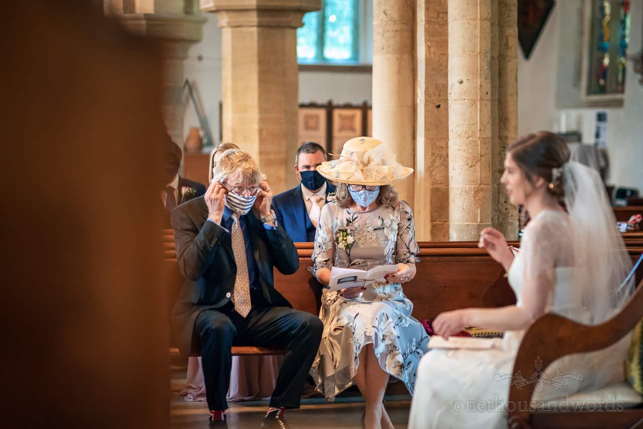 Father of the bride adjusts his COVID facemask at church wedding ceremony