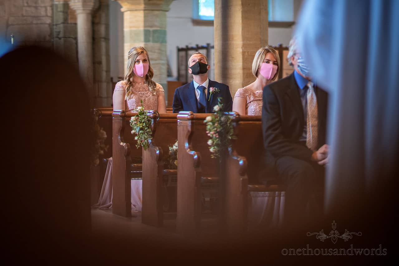 Intimate wedding photography of wedding party in covid facemasks look at church ceiling during wedding ceremony