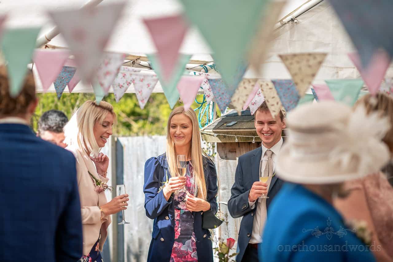 Blonde wedding guests laughing and enjoying champagne