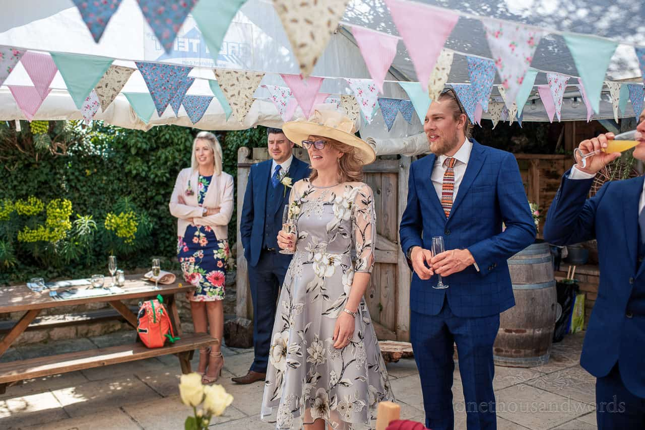 Wedding guests stand under bunting to happily welcome bride and groom to their drinks reception