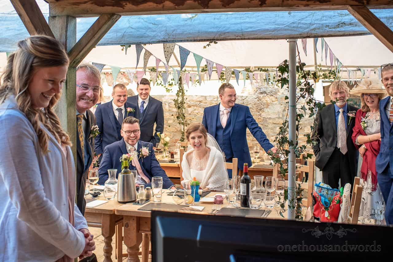 Wedding party laughing as they react to wedding messages video on TV at reception