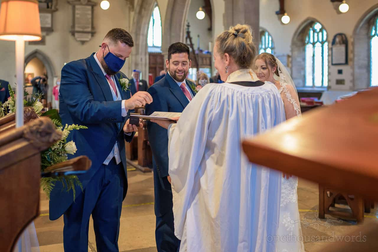 Best man in blue wedding suit and blue COVID facemask delivers wedding rings to vicar at church wedding ceremony