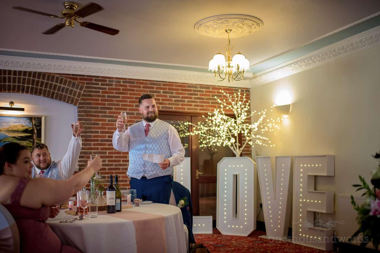 Best man in waistcoat raises glass at Springfield Hotel wedding breakfast speeches