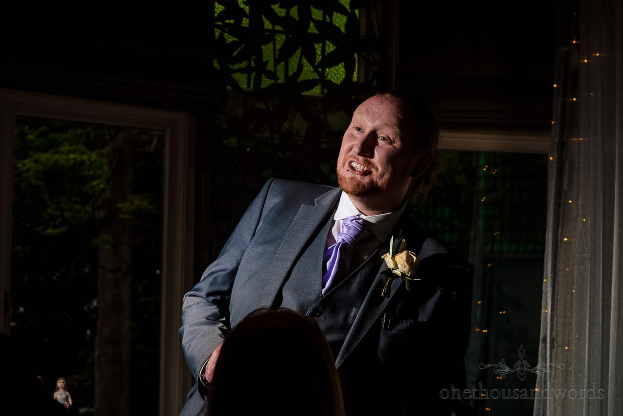 Happy best man makes wedding speech with illuminated bride cake topper
