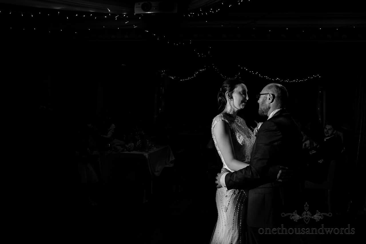 Black and white photo of bride and groom's first dance under fairy lights
