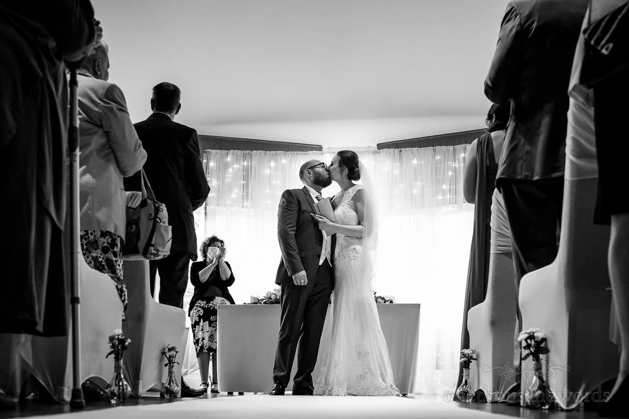 Black and white documentary wedding photo of first kiss during wedding ceremony at Bournemouth Hotel venue by one thousand words wedding photography