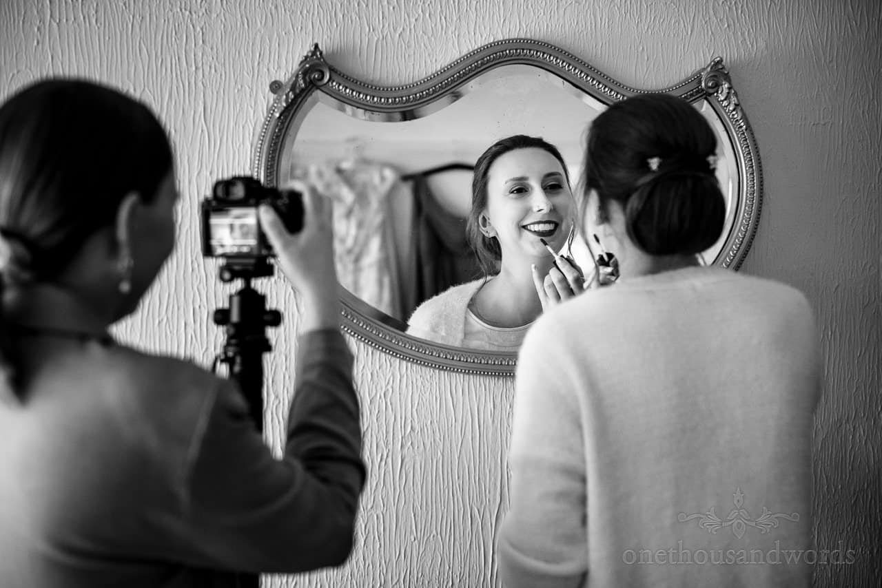 Black and white documentary wedding photograph of bride applying wedding makeup in mirror