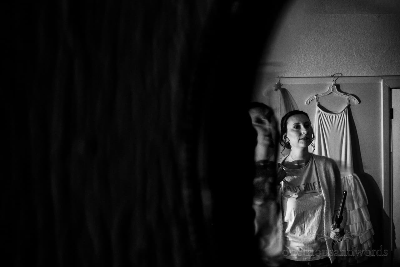 Black and white docu photo of bride styling wedding hair in mirror during bridal preparations
