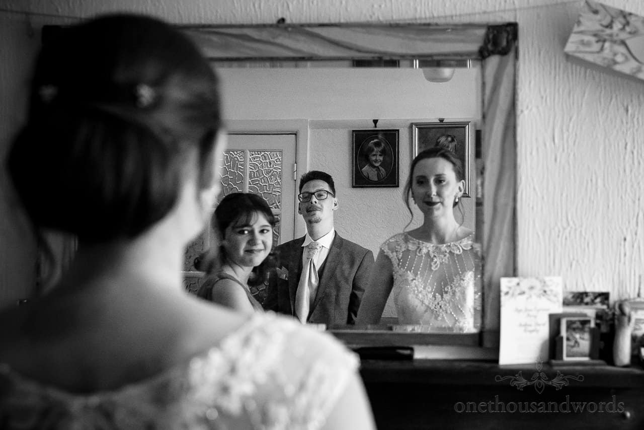 Black and white photo of bride's man watching bride and bridesmaid in mirror on wedding morning