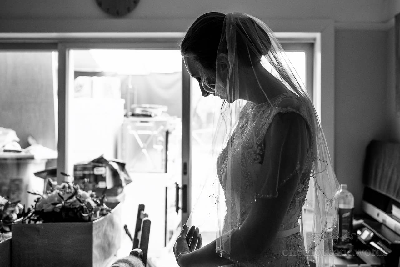 Black and white phot of bride in detailed with wedding dress and veil