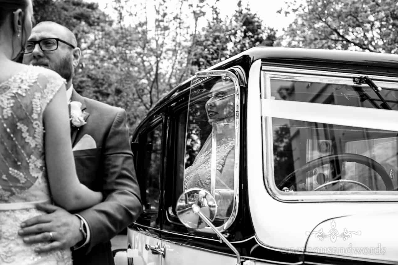 Black and white documentary wedding photo of bride's reflection in classic wedding car window