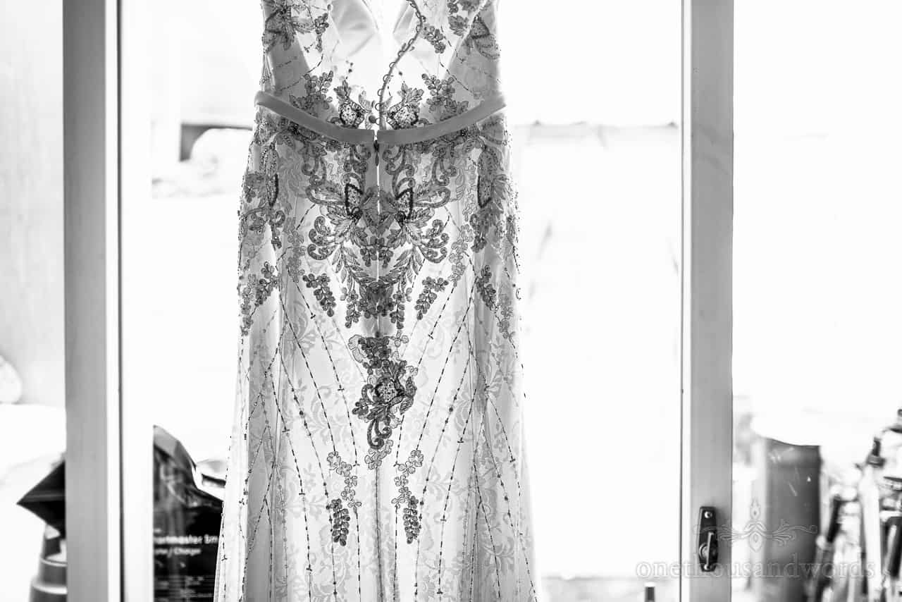 Black and white photo of lace detail on glowing hanging wedding dress