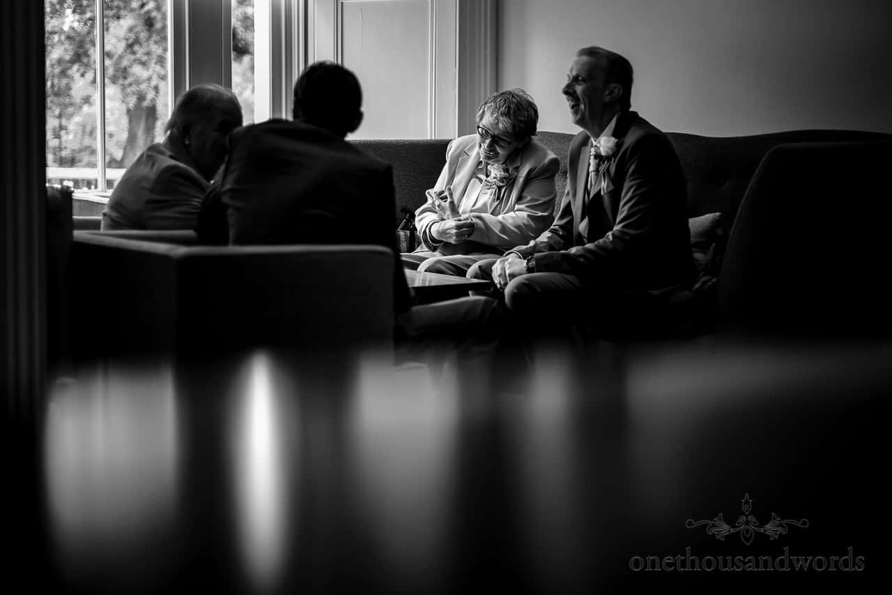 Black and white documentary wedding photo of wedding guests relaxing at The Green House wedding venue in Bournemouth