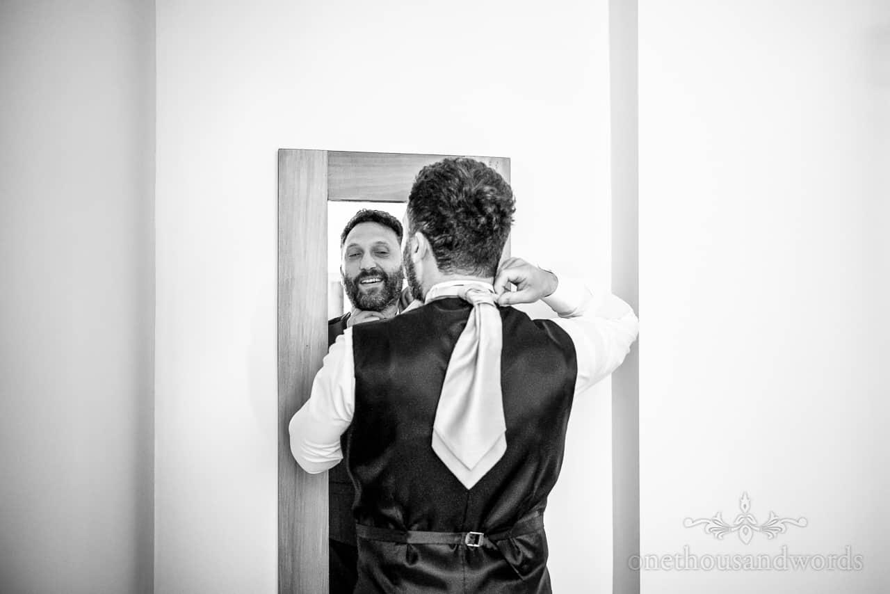 Black and white wedding preparation photo of groomsman tying tie in mirror