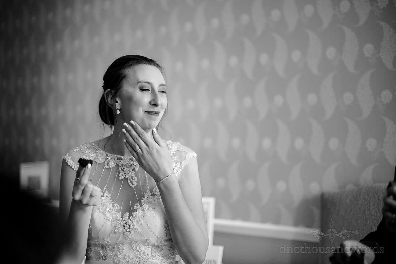 Black and white photo of laughing bride eating canapes