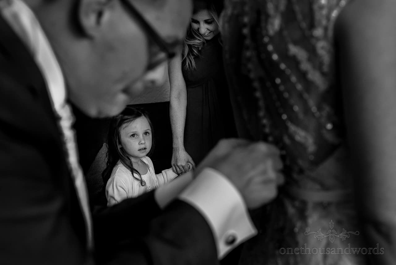 Black and white documentary wedding photo of flower girl watching bride being buttoned into wedding dress