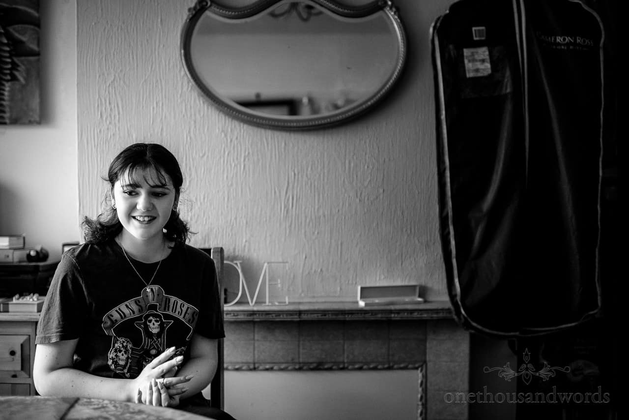 Black and white documentary wedding photo of happy bridesmaid in Guns & Roses t shirt