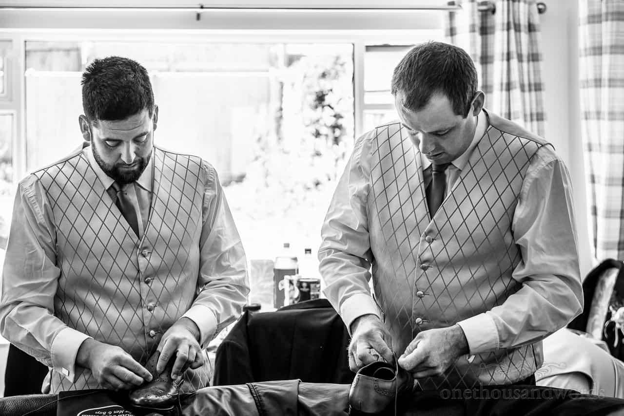 Black and white wedding photo of groomsmen lacing up brogue wedding shoes on wedding morning