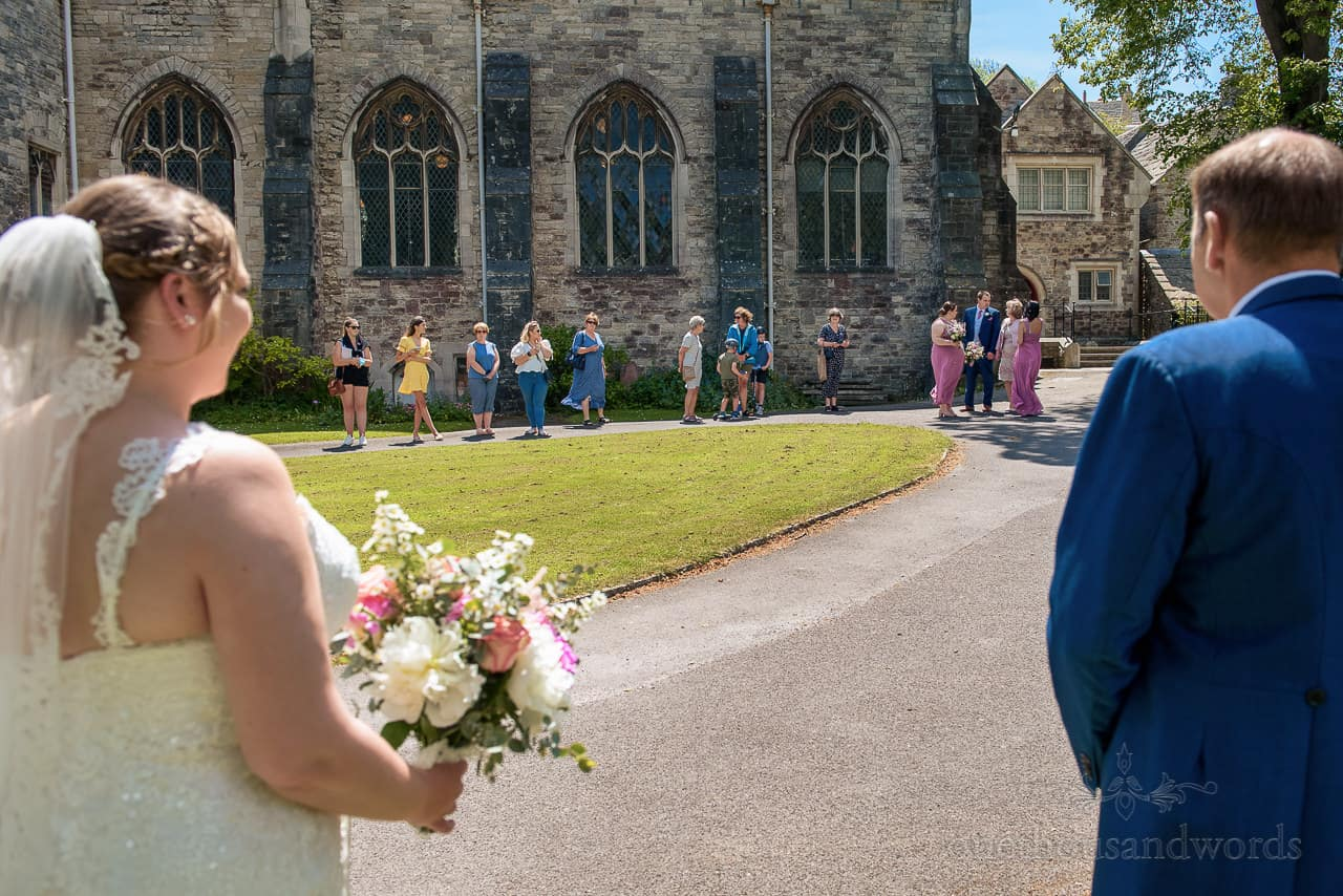 Bride and father watch wedding guests outside Dorset stone church wedding venue in Swanage