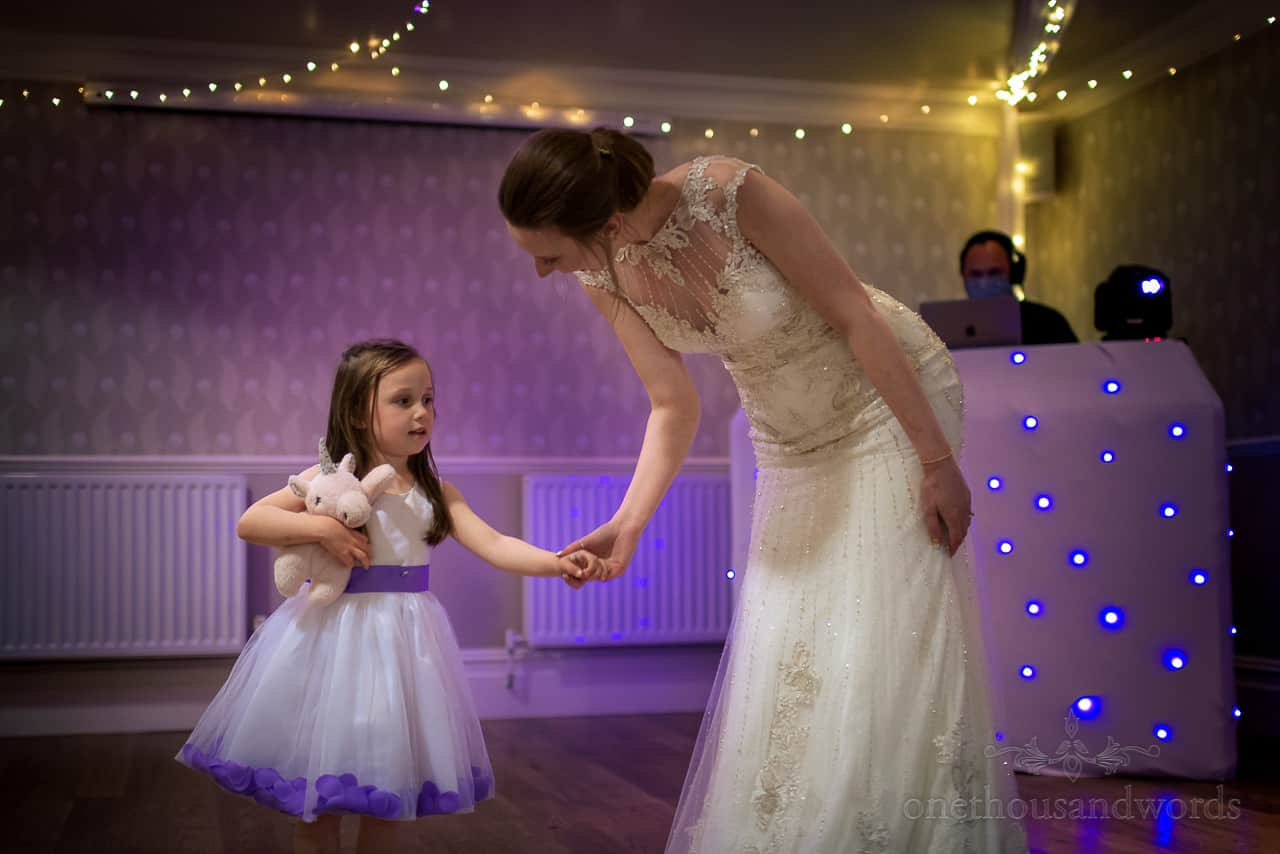 Bride and flower girl with soft toy hold hands on Hotel dancefloor