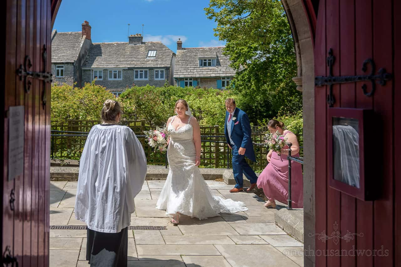Bride and father greeted outside St Mary's church doorway in Swanage by vicar before wedding ceremony