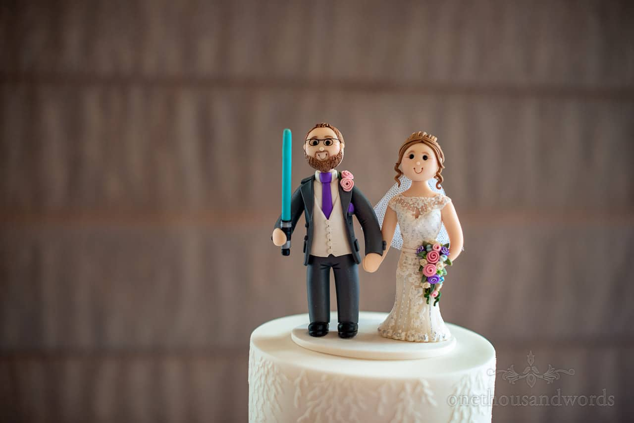 Bride and groom edible cartoon like personalised cake toppers with light sabre