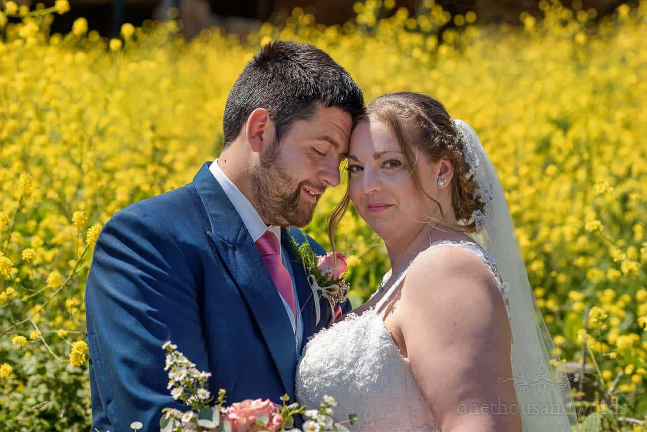 Bride and groom couple photograph taken in front of yellow countryside flowers