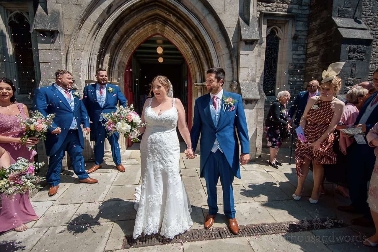 Bride and groom exit St Mary's church in Swanage to wedding guests throwing confetti