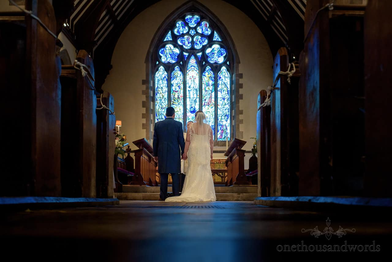 Bride and groom hold hands in front of stained glass window at Dorset church wedding ceremony