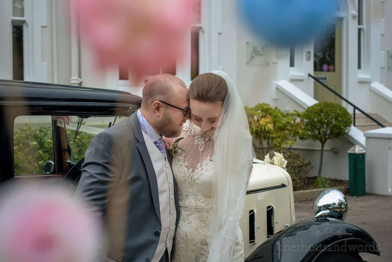 Bride and groom nuzzle next to classic wedding car outside Bournemouth Hotel venue