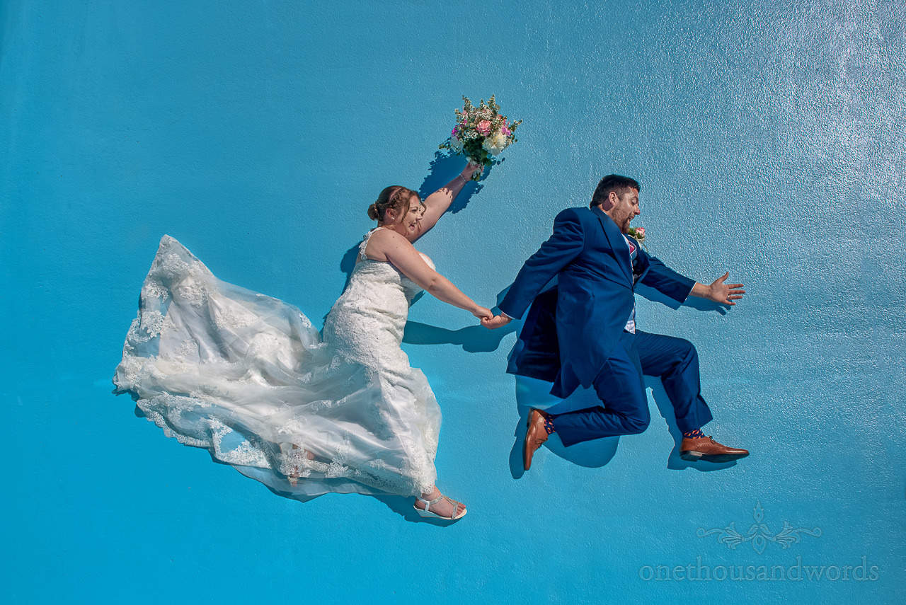 Bride and groom running in the air in empty blue swimming pool at The Springfield Hotel wedding venue