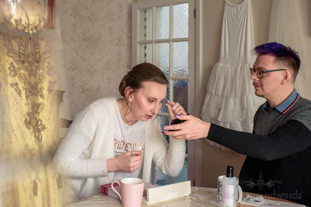 Bride is helped with false eye lashes with wedding dress reflection photograph