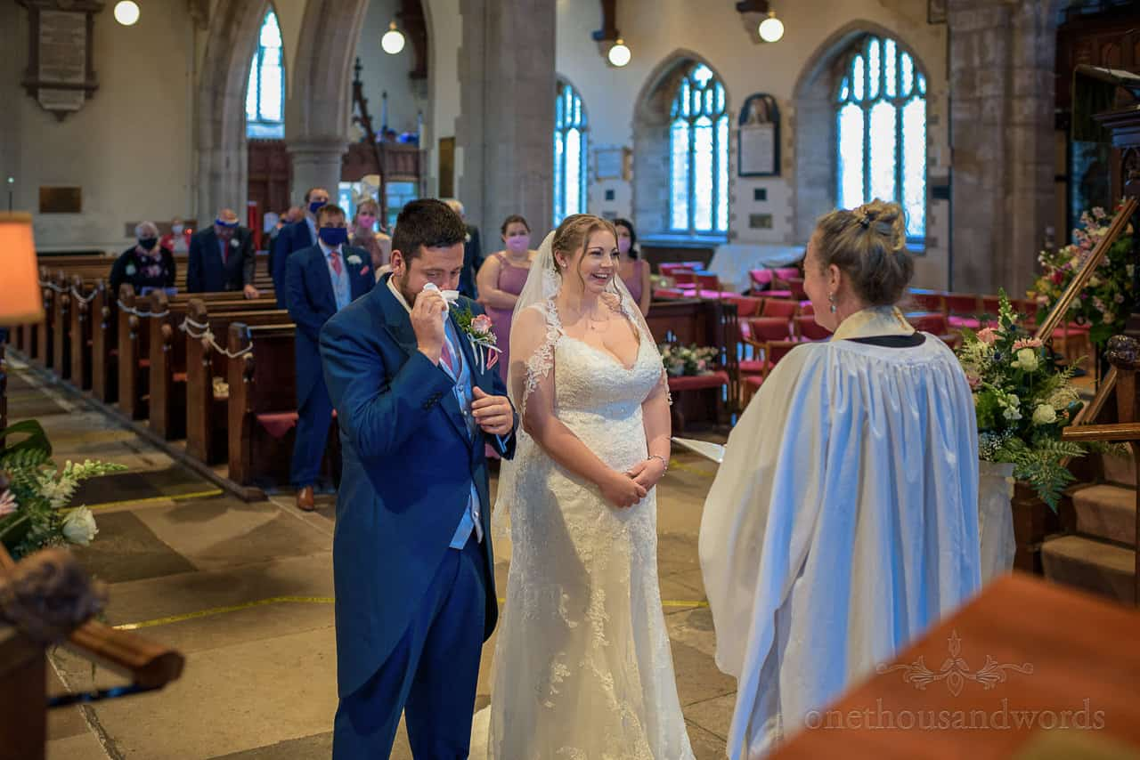 Bride laughs as groom wipes tears away at church wedding ceremony in Dorset