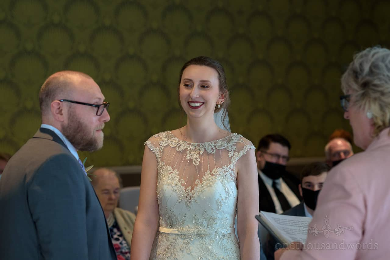 Bride smiles at groom during Bournemouth Hotel civil wedding ceremony