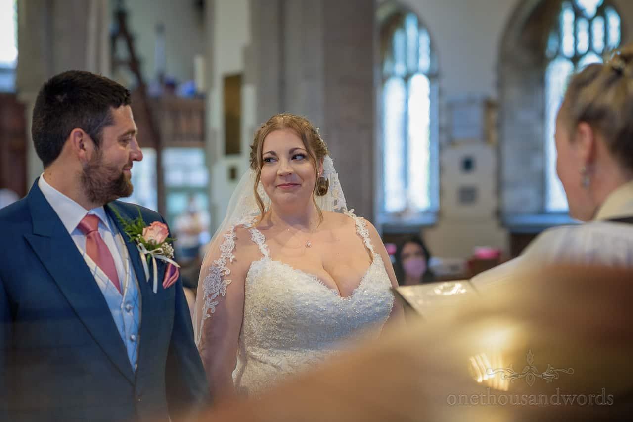 Bride smiles at groom during Dorset church wedding ceremony