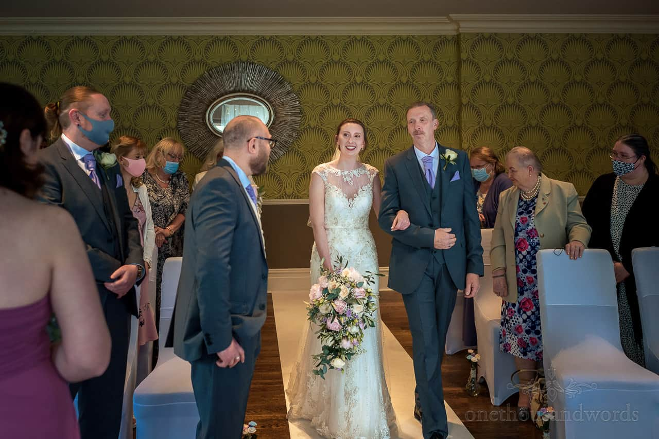 Bride is walked down the aisle by her father at The Green House Hotel Bournemouth wedding photo