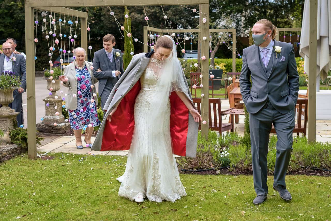 Bride walks through The Green House Hotel gardens wearing long coat with red silk lining