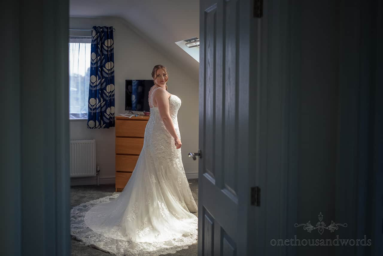 Bride in white A line lace detail wedding dress in family home on wedding morning