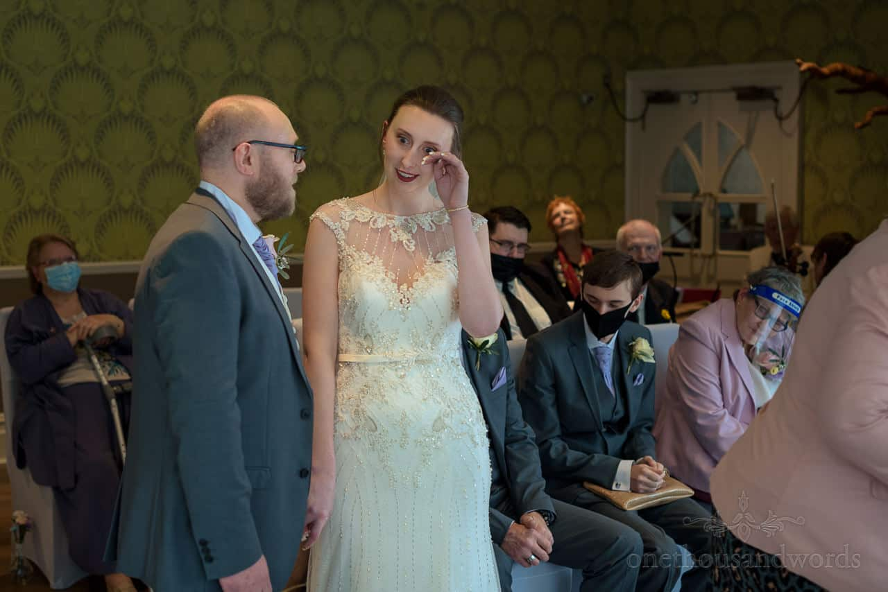 Emotional bride wipes tear from her eye during The Green House Hotel wedding ceremony in Bournemouth, Dorset