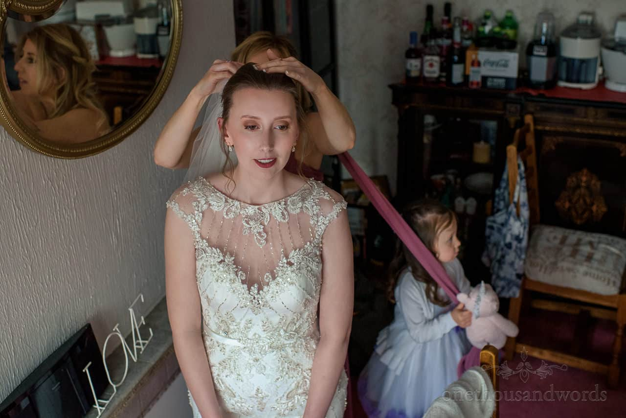 Bridesmaid puts veil onto bride whilst flower girl pulls her dress on wedding morning