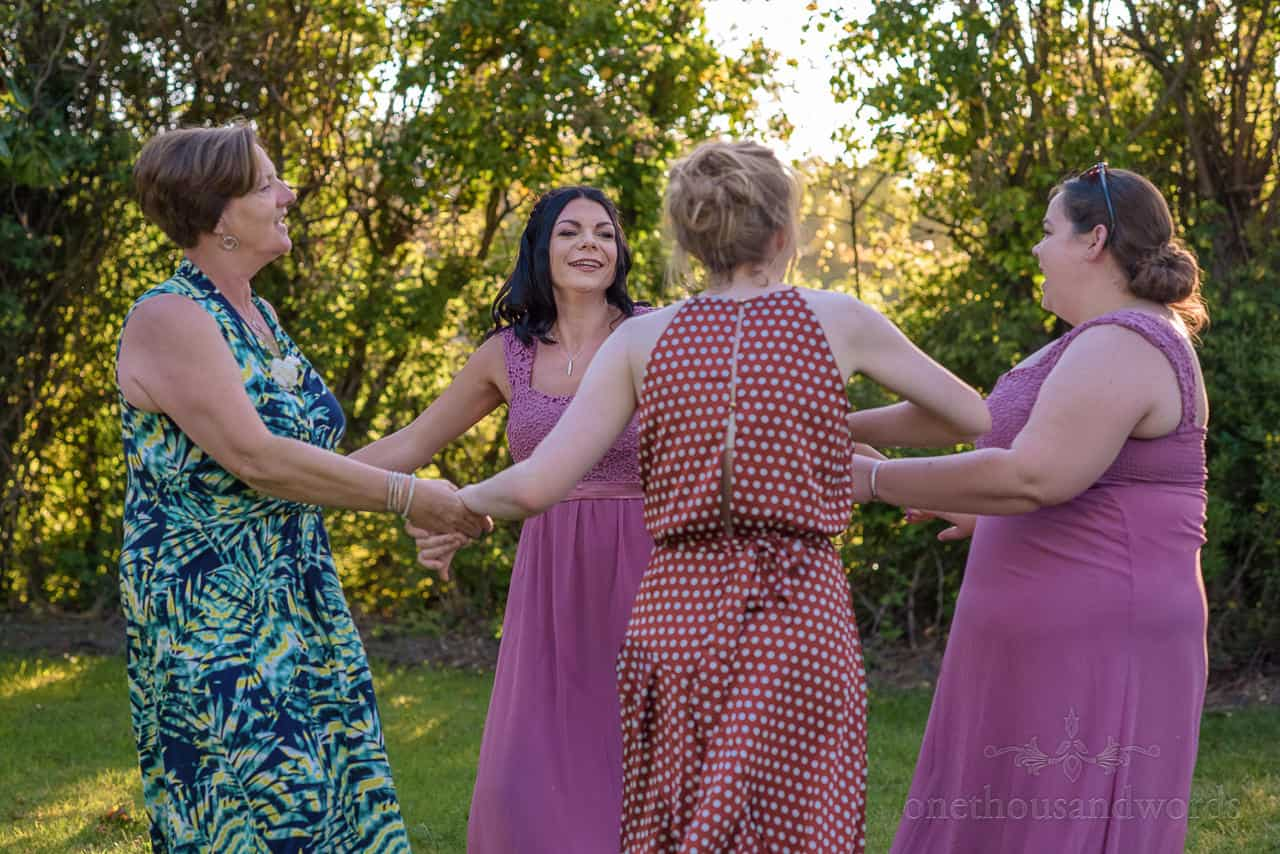 Bridesmaids and wedding guests dancing outside in hotel gardens at sunset
