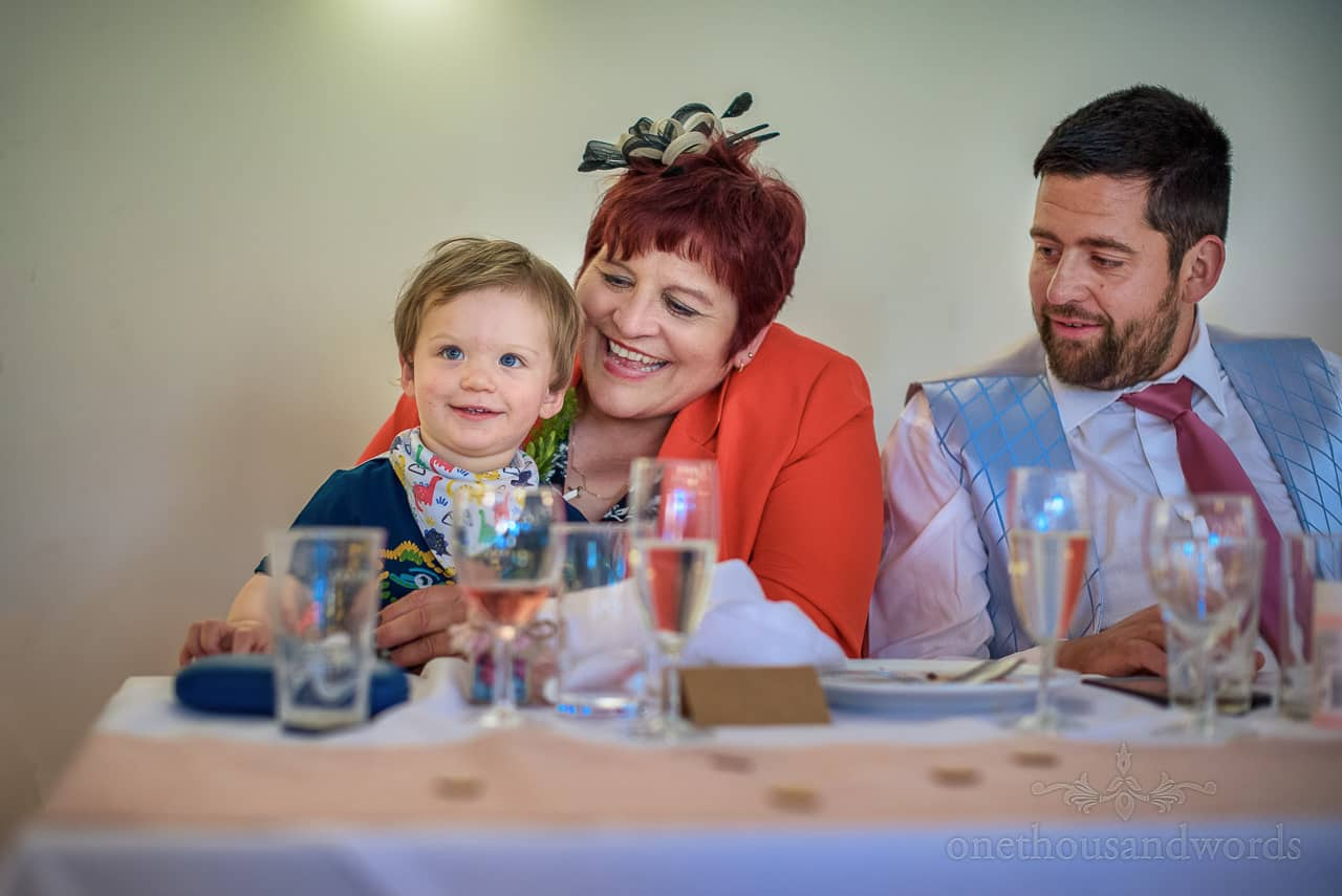 Happy child wedding guest laughing with mother of the groom at top table