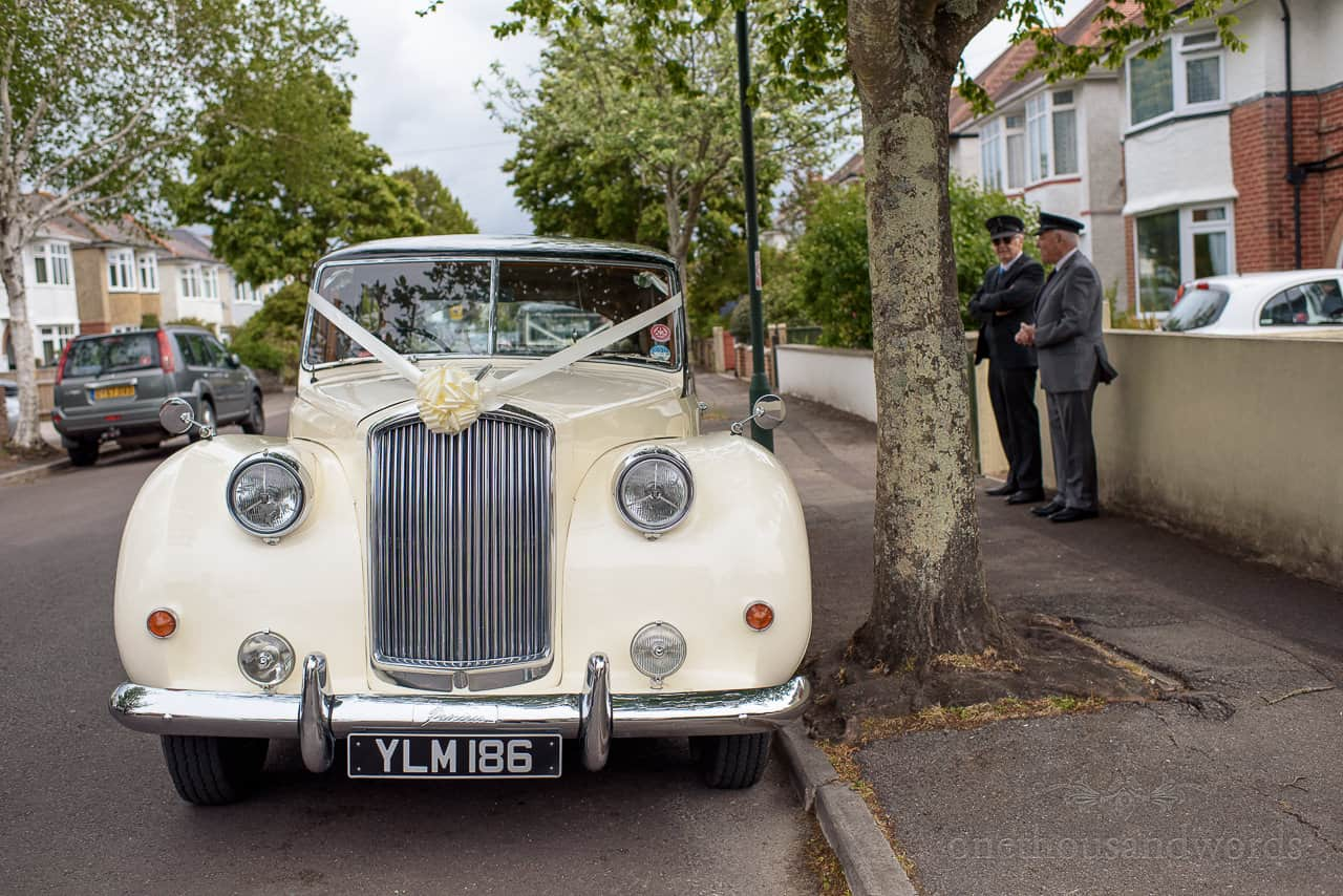 Classic wedding car photo with drivers outside bride's family home in Bournemouth
