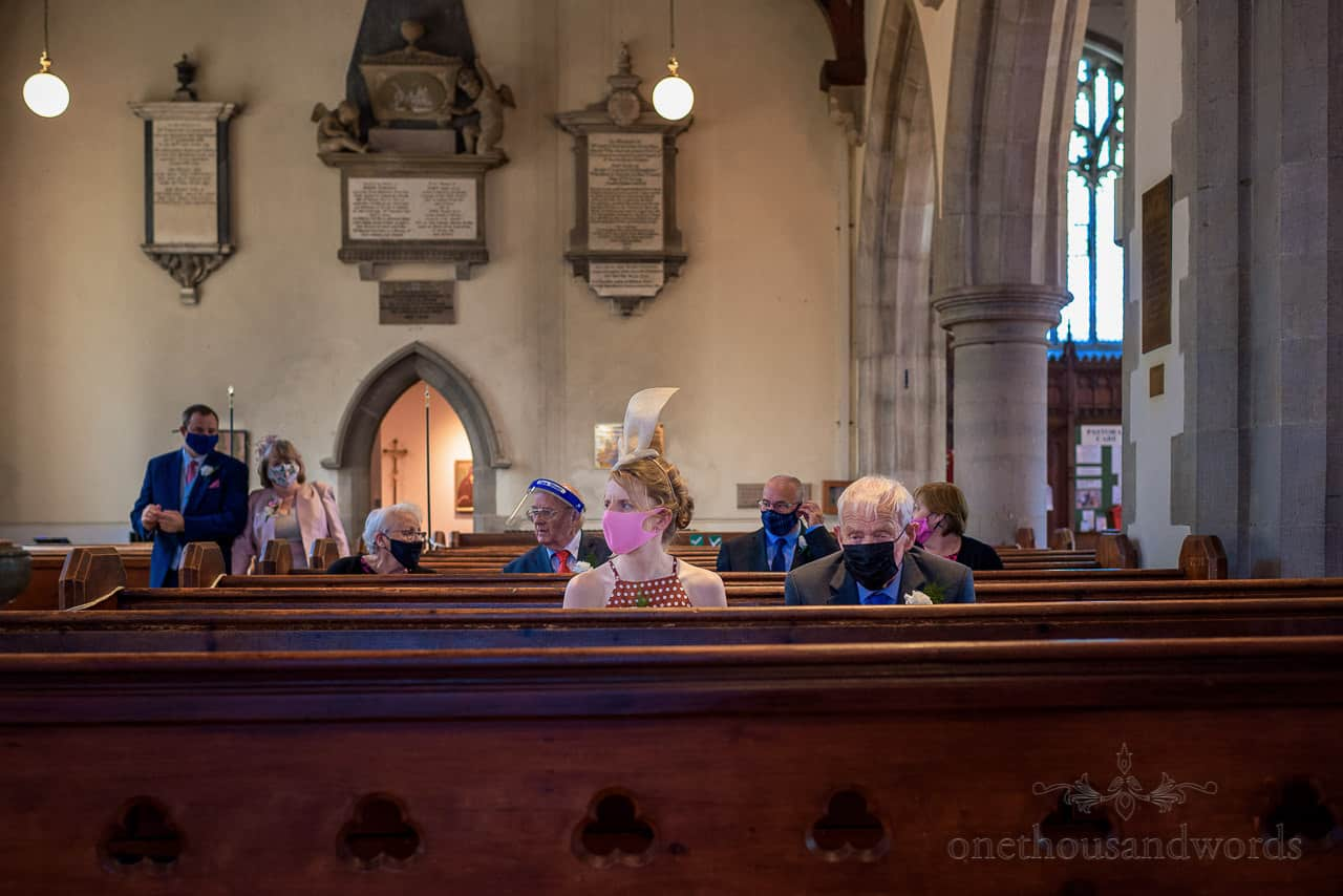 Covid secure church wedding guests in face masks and visors