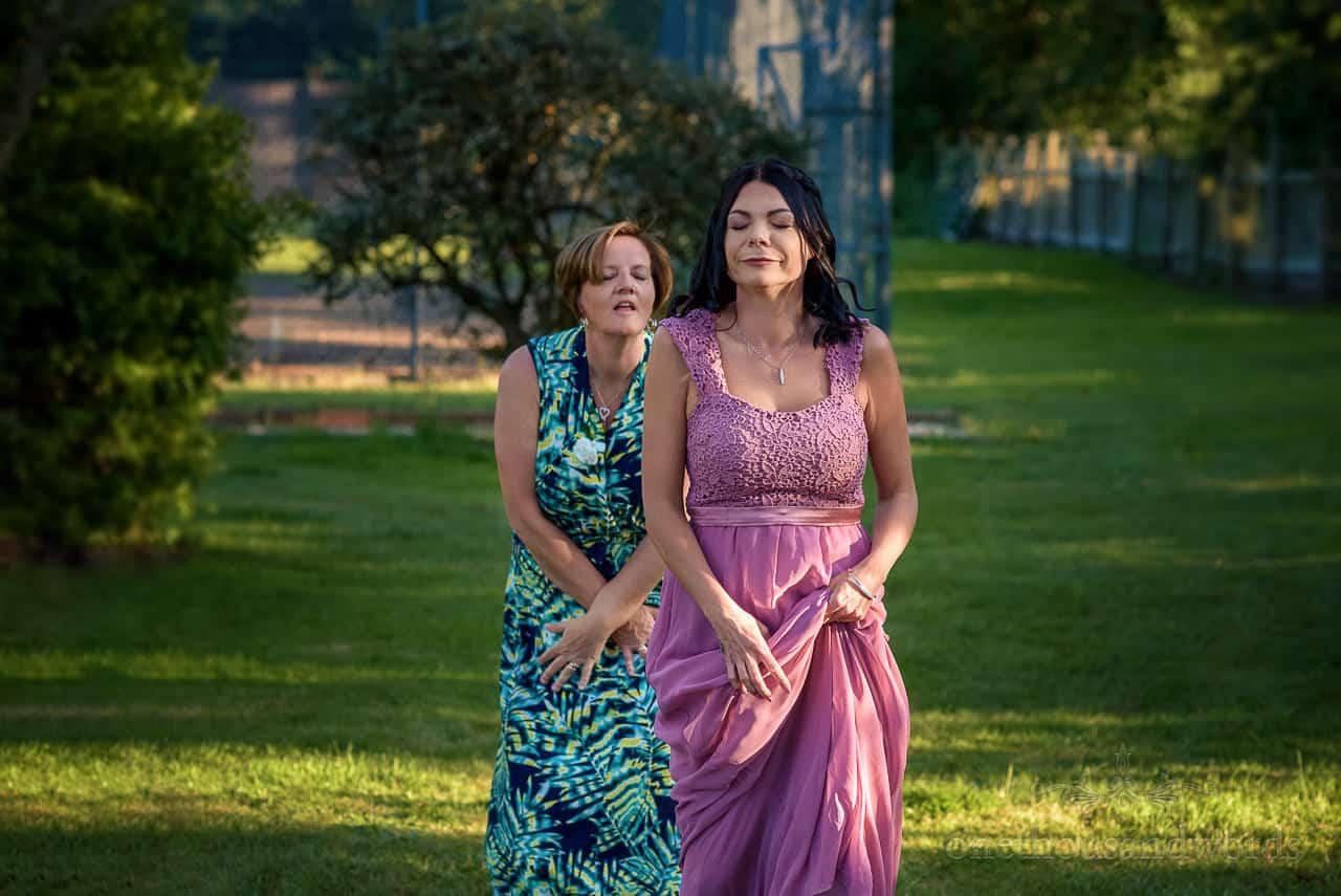 Bridesmaid and wedding guest dance routine in hotel wedding gardens