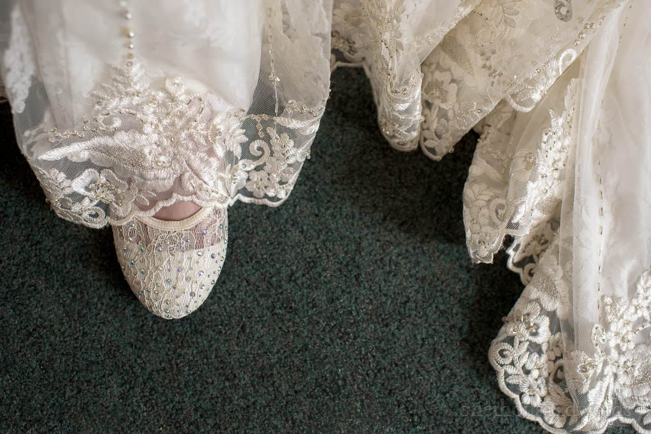 Detail wedding photograph of lace wedding shoe with wedding dress train