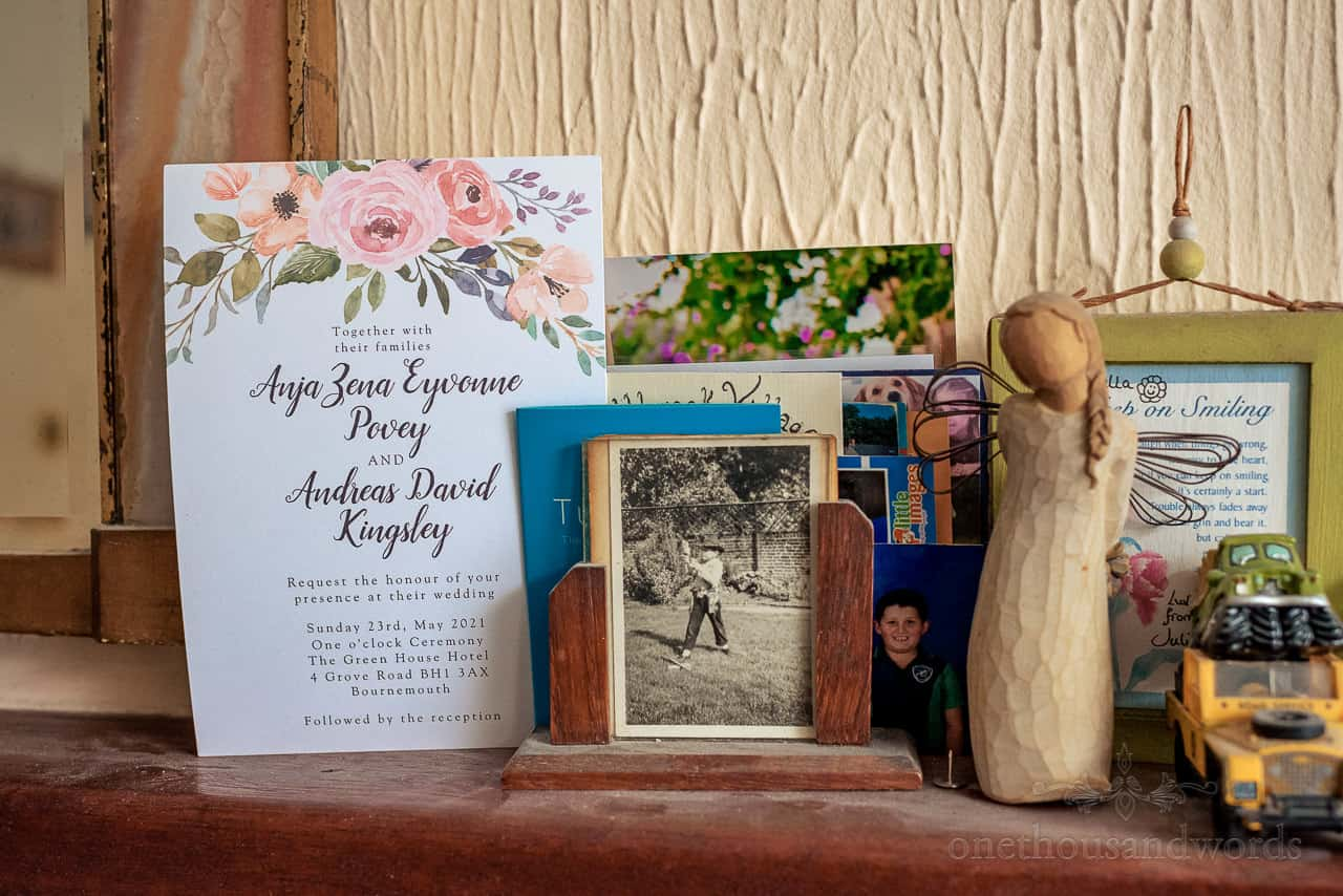 Detail wedding photograph of wedding invite on family mantle piece on wedding morning
