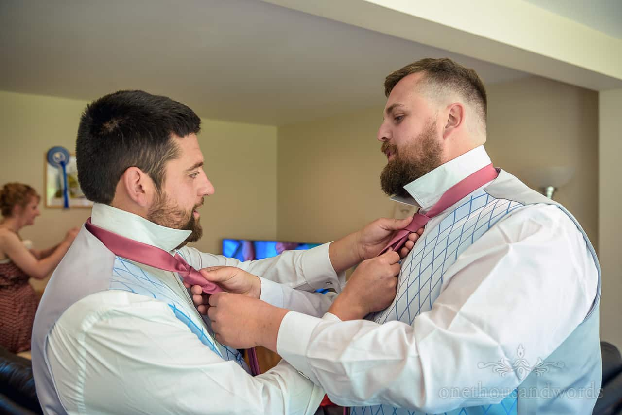 Documentary groom preparation photo of chaps tying each others pink wedding ties